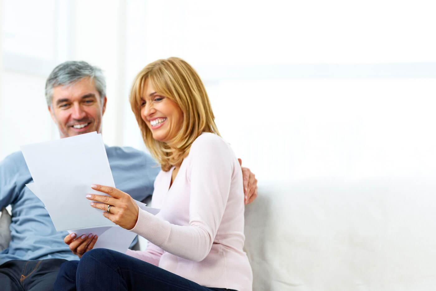 An older man and woman sitting down and smiling at their electricity bill