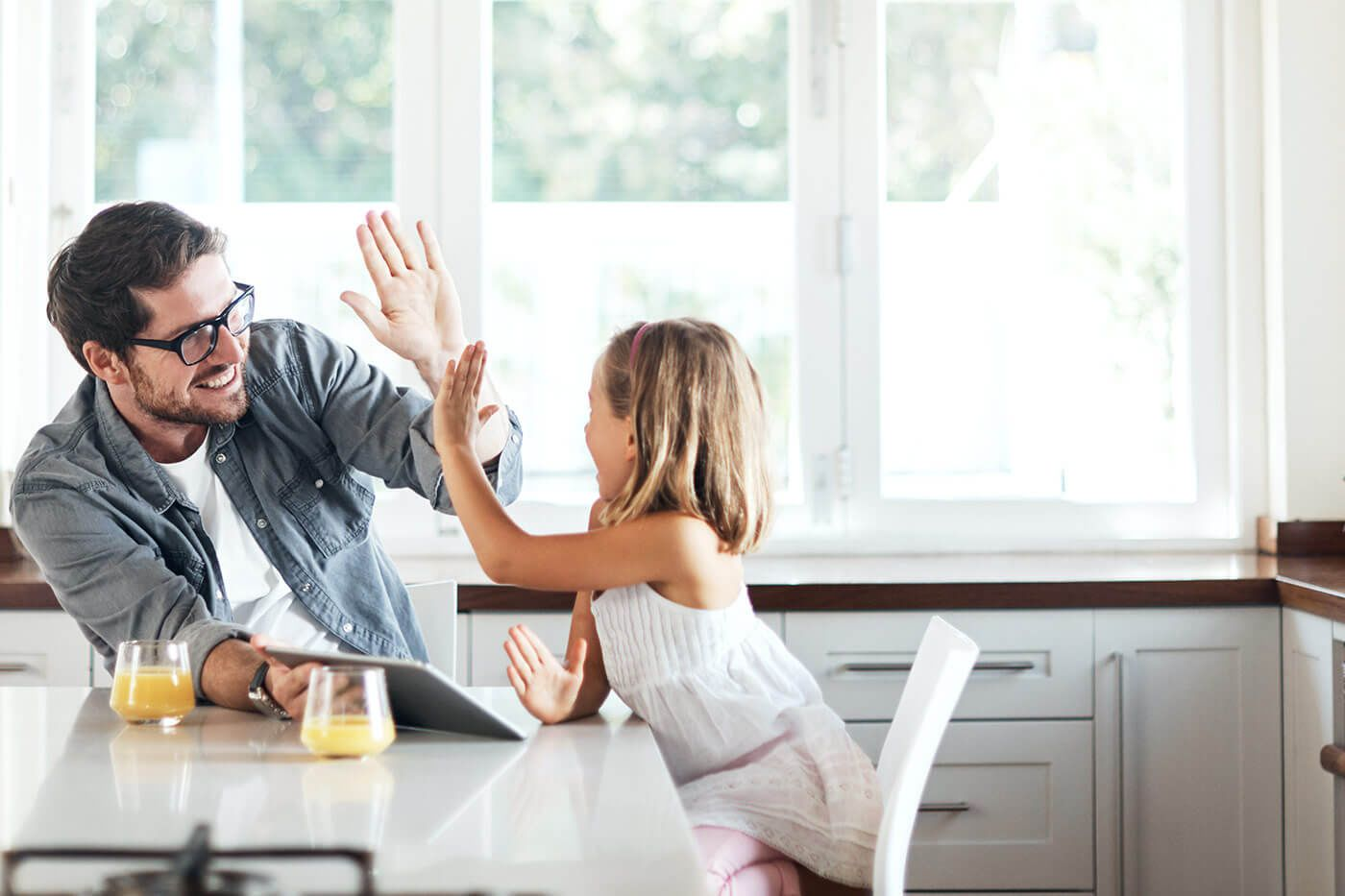 A dad giving his daughter a high-five in the kitchen while holding a tablet