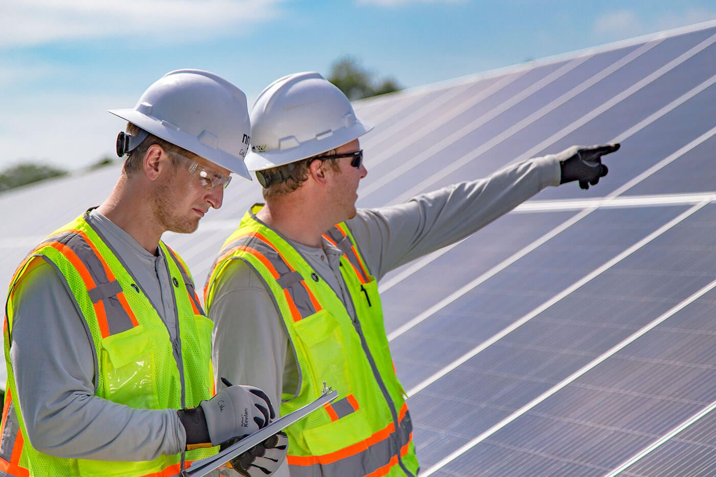 Two men in hard hats checking the solar panels