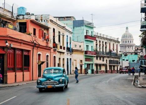 seguro viagem cuba - rua com casas coloridas e um carro clássicocarro