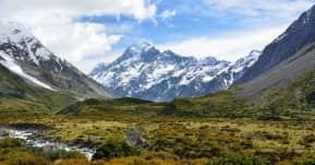 seguro viagem oceania - campos verdes com montanhas nevadas ao fundo