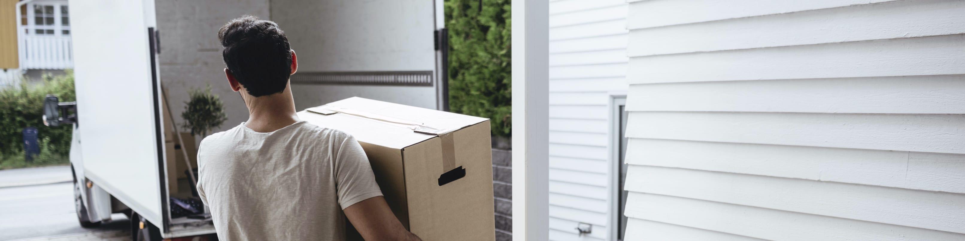 Mann räumt Kartons in den Transporter.