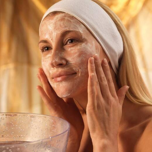 Mulher fazendo uma limpeza de pele em casa
