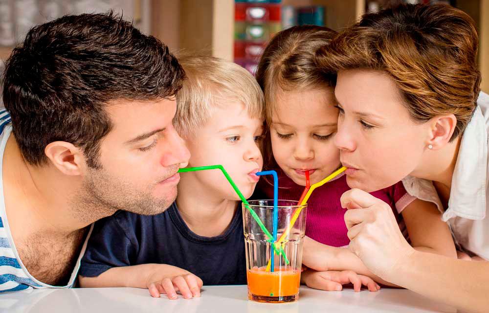 Jovem casal com seus dois filhos tomando num mesmo copo um suco de laranja com cenoura pelo canudinho