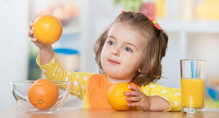 Menina de 5 anos tomando suco de laranja e absorvendo vitamina C. Ela está com 2 laranjas na mão e um copo de suco de laranja ao lado.