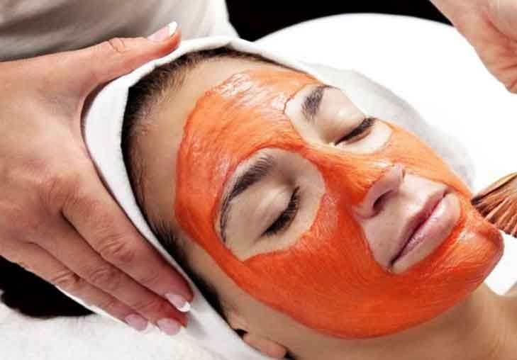 Benefícios da cenoura para a pele. A imagem mostra uma mulher fazendo uma limpeza facial usando a cenoura.