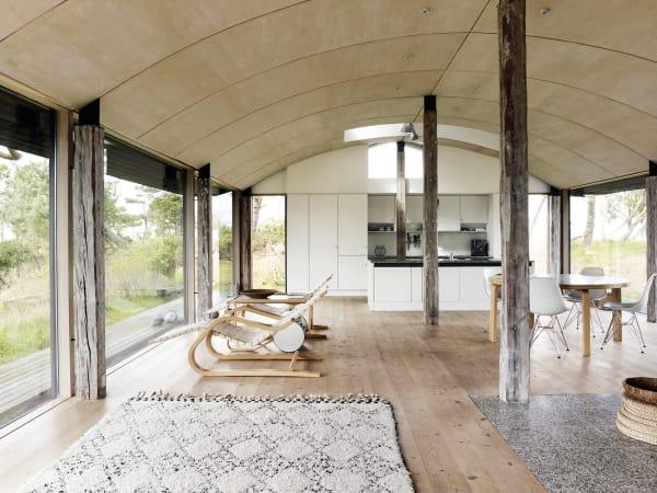 Der Großteil der Möbel ist von Alvar Aalto; nur für die Esszimmerstühle sind Charles und Ray Eames verantwortlich. Die gekrümmte Decke über Salvage-Balken verkleidete Knud Holscher mit einfachem Sperrholz, das sich biegen und in großen Bahnen statt einzelner Bretter verlegen lässt.