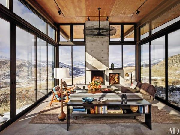 Die Glaswände des Hauptpavillons sind verschiebbar, sodass im Sommer ein komplett offener Raum geschaffen werden kann – während man im Winter an der kuschelig warmen Feuerstelle sitzt. Die Sessel wurden mit Vintage-Decken bezogen.