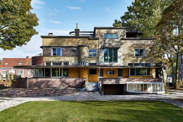 """Nicht weniger als vier Ziegeltöne gliedern die Fassade der Villa horizontal. Auch mit halbrunden Bauelementen – wie Erkern, Dächern und dem Wintergarten auf der Gartenseite – knüpfte der belgische Architekt Gentiel Van Eeckhoutte an """"maritime"""" Vorbilder von Le Corbusier und Mallet-Stevens an."""