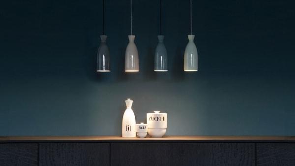 Die Leuchte basiert auf einem Entwurf einer Flasche von Theodor Bogler, aus dem ebenfalls Aufbewahrungsdosen hervorgegangen sind.