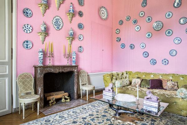 Delfter Kabinett: Auf den mit rosa Vichy-Karo-Stoff bezogenen Wänden blühen Fayenceteller aus Delft, Rouen, Nevers und Sèvres blau-weiß auf. Wie der Bronzetisch und der antike Nain-Teppich reizt auch der anisfarbene Seidensamt des Sofas die Fingerspitzen.