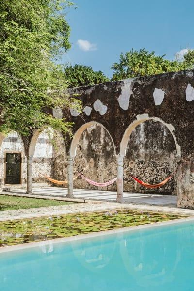 Ein umlaufender Seerosenteich, der an den großen Pool stößt, prägt        das Bild des Anwesens. Auch in den bunten Hängematten hat man freie        Sicht aufs Wasser.