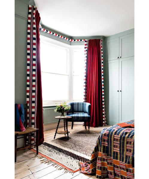 """Das Fenster im Schlafzimmer rahmte Guinness mit Leinen von Designs of the Time, eingefasst von Jennifer Shortos """"Swing Landscape"""" in Union Jack-Farben."""