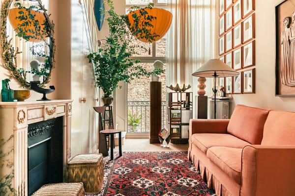 """""""Der lachsrosa Sofabezug war zuerst da, dann kamen der iranische Teppich        aus den 50ern, Papas Schwarz-Weiß-Grafiken, und so ging's im        Schneeballsystem weiter"""", erzählt der Designer. """"Der Fond sollte hell        bleiben, die Wohnung war ja früher ein Künstleratelier."""" Im        Treppenaufgang verbirgt sich der Kleiderschrank, und abends hüllt        Josef Hoffmanns Lampionleuchte alles in sanftes Orange."""