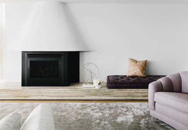Arent & Pyke fangen in einem Penthouse in Sydney elegant den Maschinenlook der Kaminkassette auf – mit geschwungener Haube, Travertinsockel und schimmerndem Teppich (von Minotti).