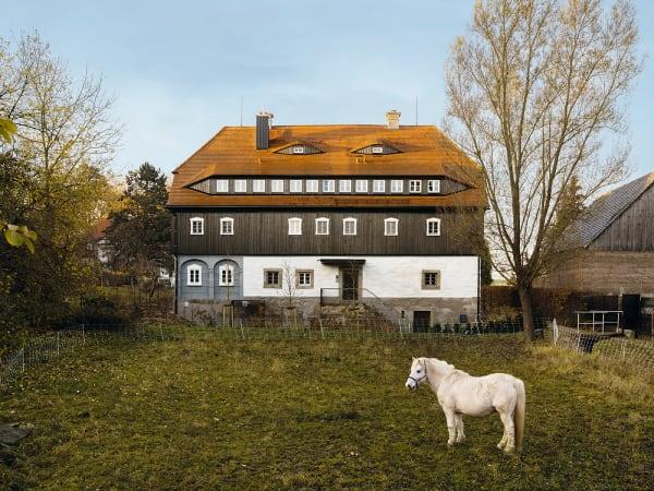 Wo einst ein Faktor mit handgewebtem Leinen Handel trieb, residiert nun        die Verwaltung des Möbelhauses Starke. Die Wiese ist verpachtet – als        Weide für ein Pferd und seinen besten Freund, ein Schaf (leider nicht        mit im Bild).