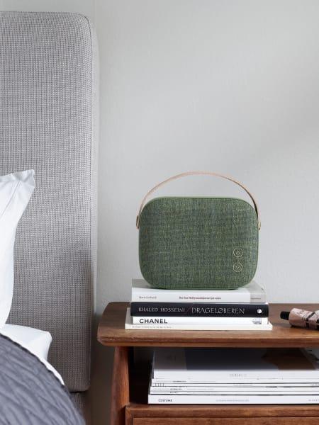 """Mit skandinavischem Design punktet """"Helsinki"""" von Vifa– nicht einfach ein Elektrogerät, sondern ein echtes Stil-Accessoire. Hochwertige Materialien wie der Textilbezug von Kvadrat (hier in """"Willow Green"""") und ein (echter) Lederriemen lassen die Box wie eine Handtasche erscheinen."""