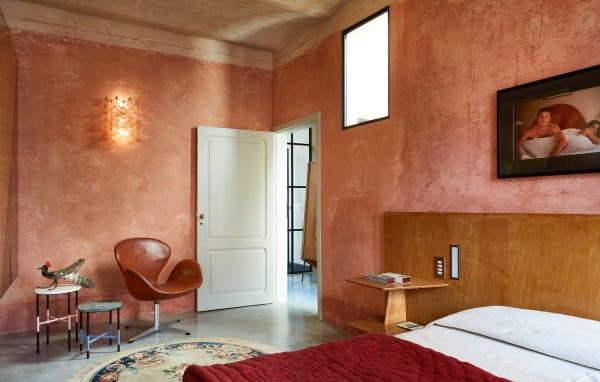 """Über dem Gio Ponti-Bett (aus dem Hotel """"Parco dei Principi"""") hängt eine Bettszene von Nan Goldin. Neben Jacobsens """"Swan"""" steht ein """"Courtesy Table""""-Paar – Seppias jüngstes Designprojekt für Nero."""