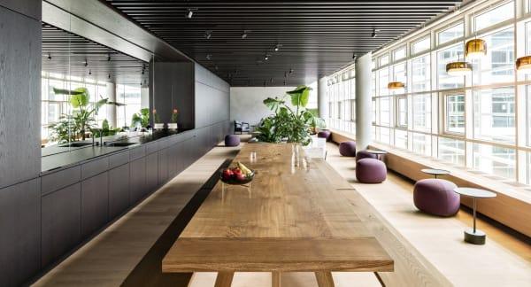 """Die luftige Lounge mit Eichenholzmöbeln vonBuchholz Berlinsteht allenCondé Nast-Mitarbeitern zur Verfügung. Wer es weicher mag, nimmt auf einem """"Kipu""""-Pouf vonLapalmaoder denFlexform-Sesseln im Hintergrund Platz.Markus Widmann Lichthalf bei der Planung und lieferte die Vistosi-Leuchten."""