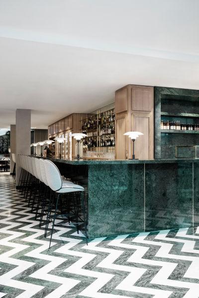 """<p>Eleganter schwarz-weißer Marmorboden, verlegt im Fischgrätenmuster. An der Bar: Gubi´s Beetle Bar Chair"""".</p>"""