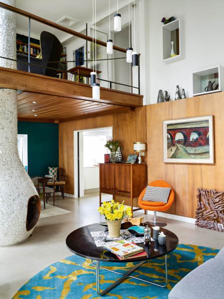 """Die Vertäfelung im gut fünf Meter hohen Wohnzimmer konnte bei der Restaurierung im Originalzustand erhalten werden, Beistelltisch und Kommode sind Vintages aus den 50ern, der orangefarbene Sessel im Arkana-Stil wurde mit dem Stoff """"Princess"""" neu bezogen. Nach dem alten Entwurf neu angefertigt ist auch die Hängeleuchte von Troughton&Young."""
