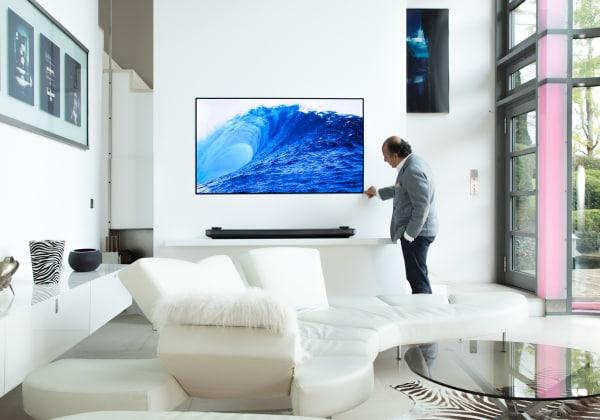 Hadi Teherani im Wohnzimmer mit dem ultraflachen LG SIGNATURE OLED Fernseher