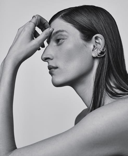 """Wie schwerelos kreisen Ring """"Ellipse"""" (8942 Euro) und Ohrringe """"Infinité"""" (858 bis 1628 Euro) um den eigenen Körper. Planetenbahnen inspirierten Shannon Nataf zu ihren Entwürfen aus Gelbgold und weißen Diamanten."""