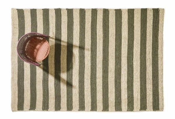 """Der olivgrün-flachsfarbene Teppiche """"par raya"""" wird in Handarbeit aus einer agavenähnlichen Pflanze hergestellt. Von der zweifarbig gestreiften Serie sind fünf verschiedene Farbkombinationen sowie drei Größen erhältlich."""