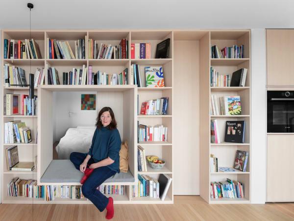 Die Eigentümenin Elisabeth Brizard umgeben von ihrer großen Leidenschaft: ihren Büchern. Der Einbau aus Eschenholz trennt Wohn- und Schlafzimmer. Druch das integrierte Sitzfenster kann sie sogar vom Bett aus den Sonnenaufgang und die Alpen sehen.