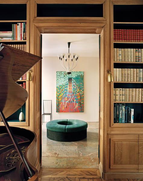 """Es ist offen! Jeremy Demesters Gemälde """"Le Couvent"""" empfängt im Entree, und unter Carlo Scarpas Lüster kringelt sich Pouf """"Donut"""" von Pierre Yovanovitch. Die Bibliothek aus Eiche ließ Frank einst sandstrahlen."""