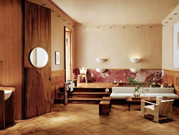 """An der Wand der """"Folk Chair"""" von Studio Giancarlo Valle, vorne eine table basse von George Nakashi- ma. Hinter der Nussbaumtür versteckt sich ein skulpturales Waschbecken."""