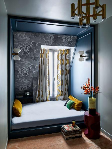 """Zum Schlafen und Entspannen installierten die Interiordesigner Emil Humbert und Christophe Poyet im kleinen Gästezimmer ihrer Pariser Mansarde eine Art Schein- Nische. Zwischen die taubenblauen Wände fügten sie dafür einen in Farrow& Balls dunklerem """"Hague Blue"""" lackierten Holzrahmen. Der Teppich ist von Stepevi, die Fornasetti-Tapete in  der Schräge von Cole&Son."""