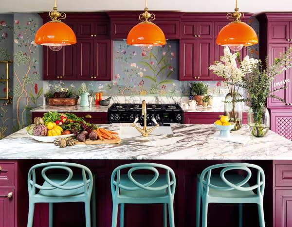 In der Küche kontrastiert der Magentaton der Fronten mit Arabescato-Marmor, die Leuchte hing einst über einem Billardtisch. Stühle von Janus et Cie.