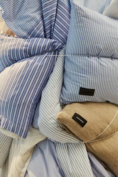 """Der himmelblaue Baumwollstoff ist inspiriert von einem Businesshemd, macht sich aber als Bettwäsche ebenso gut. Dessen Partner in crime: Leinenkissen """"Cottage""""."""