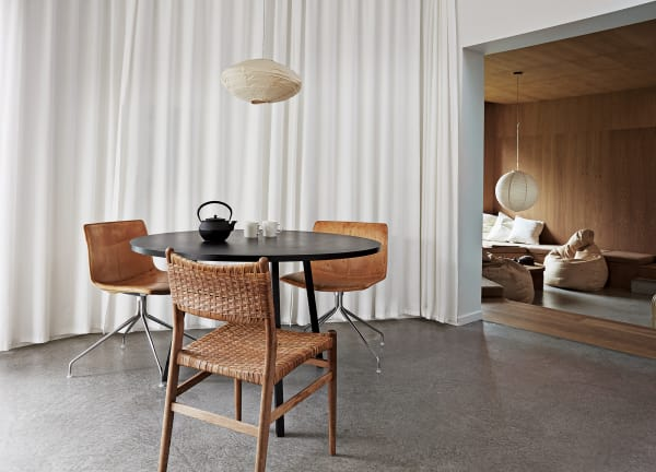 In der Küche, die über eine Stufe direkt ins Wohnzimmer daneben führt, kombinierten die Hausherren einen Hay-Esstisch mit Lederstühlen von Arper. Den Vintage-Korbstuhl im Vordergrund entdeckten sie auf einem Flohmarkt.