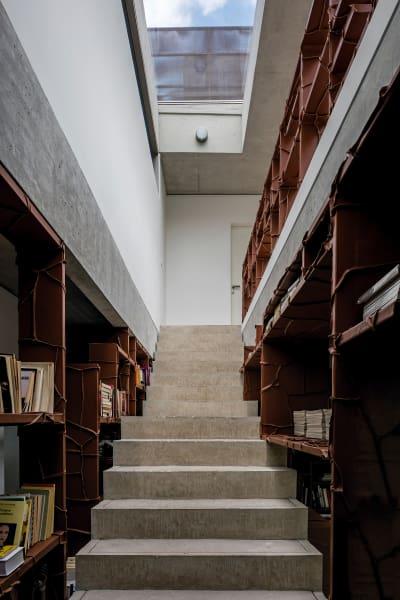 Beim Betreten der Treppe aus Sichtbeton wird man von rund tausend Büchern in einem von Leder umwickelten Regal begleitet.