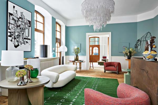Das Pferd an der Wand beäugt Delcourts Möbel auf dem grünen        Cogolin-Teppich.