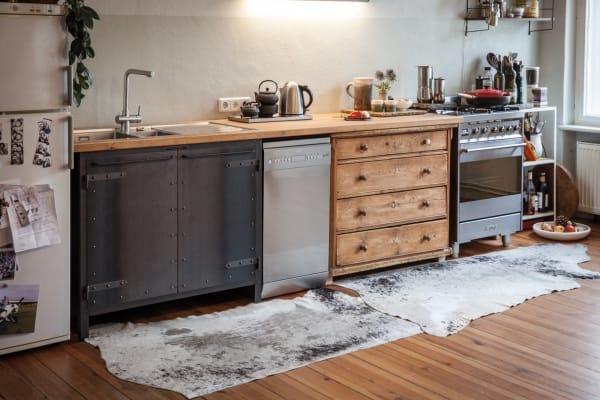 """Nicht zu """"küchig"""" wünschte sich eine Berliner Bühnenbilderin das Ambiente. Also verzichtete sie bewusst auf Fliesen und integrierte eine antike Kommode in die Küchenzeile von Authentic Kitchen – genauso selbstverständlich, wie sie auch im Rest der Wohnung Flohmarktfunde mit Neuem mixt."""