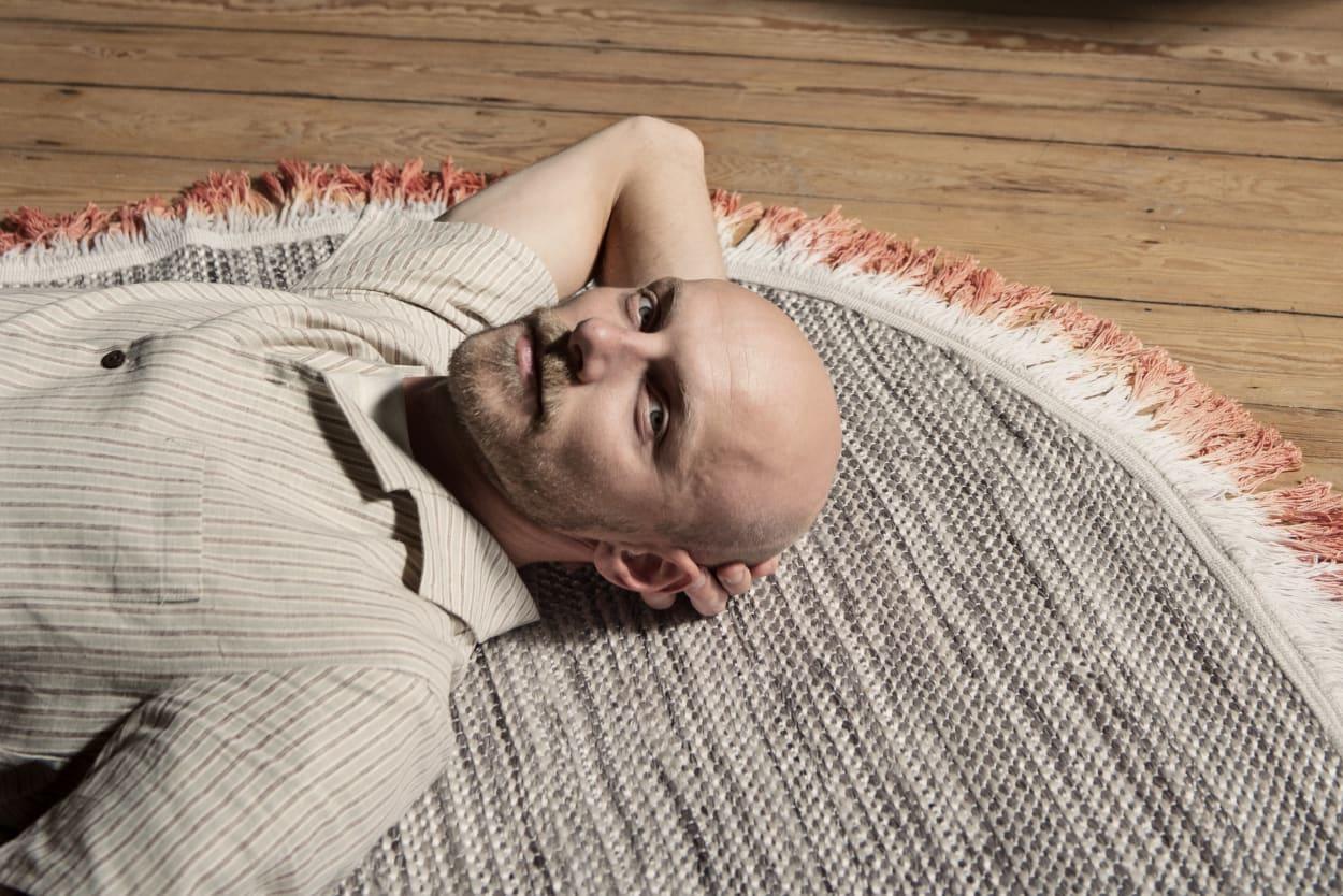 """Designer Sep Verboom auf seinem Teppich """"Rope"""" liegend"""