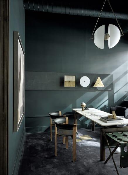 """Der dunkelste Ort im Apparatus-Apartment ist das Büro von Jeremy        Anderson. An der Wand reihen sich Appliken der """"Buddies""""-Serie aus        Kupfer und handbemalter Email, für die sich die Desi-gner von Kasimir        Malewitsch anregen ließen. Den Tisch mit weißer Marmorplatte entwarf Le        Corbusier für Cassina."""
