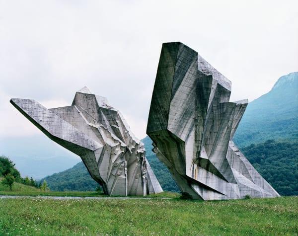Tjentište:Als wären Sedimente aus  dem Erdinneren emporgeschleudert worden: Die  beiden kantig-schroffen  Betonelemente in den bosnischen Bergen schuf  Miodrag Živković 1971. Nahezu zwanzig Jahre wurde an dem Nationalpark um das abstrakte Monument gearbeitet. Es erinnert an eine Partisanenschlacht im Sommer 1943.