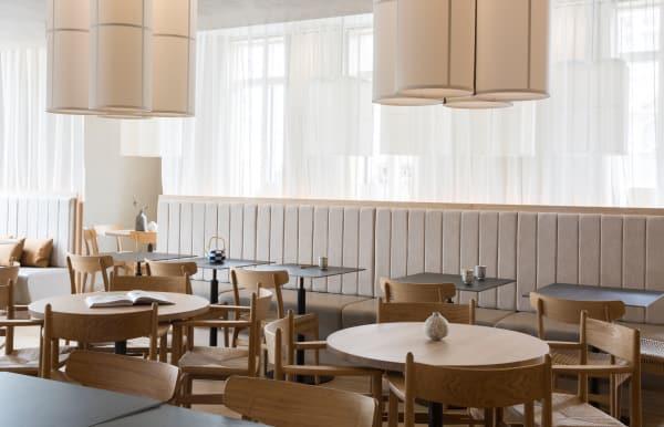 Im Restaurantbereich dominieren helles Eschenholz und klassische Carl Hansen und Søn-Stühle.