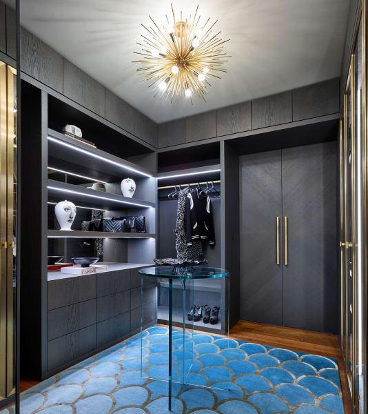 Die Ankleide aus Eiche mit Messingdetails richtete Justin Howlett für Euroboden Interior ein. Der Seidenteppich vonCC-Tapis und ein Sputnik-Lüster geben Glamour, Vasen und Bildbände über Mode oder Design lockern den Raum auf.