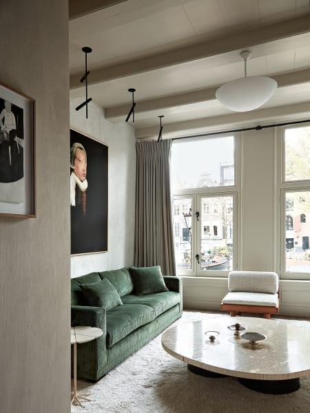 Kanal total: Den besten Blick auf  die Amsterdamer Grachten bietet  das Wohnzimmer  im ersten Stock.  Das Sofa entwarf  der Hausherr selbst; den Tisch fand er beim niederländischen Vintage-SpezialistenMorentz.