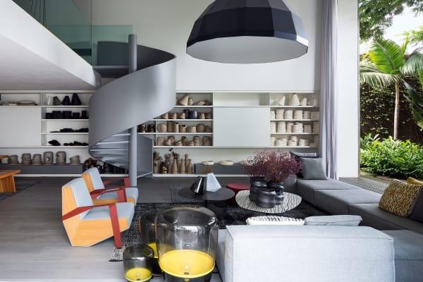 """An Claudia Issas Atelier schließt sich ein offen gestalteter Empfangsraum für Gäste an: Sessel und Tischchen von Moroso, Bodenleuchten """"Balloons"""" von Brokis. Die steingraue Wendeltreppe, ein Entwurf des Architekten Marcio Kogan, führt vom ebenerdigen Studio in den darüberliegenden privaten Teil des Hauses."""