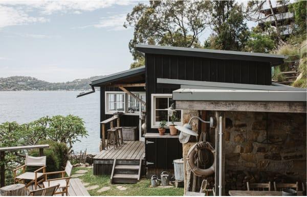"""""""The Little Black Shack"""" ist eines der kleinsten Häuser in Mackerel Beach, steht aber auf einer der größten Landflächen. Dahinter erstreckt sich die Uferpromenade bis hinauf zum Ku-ring-gai Chase National Park in New South Wales."""
