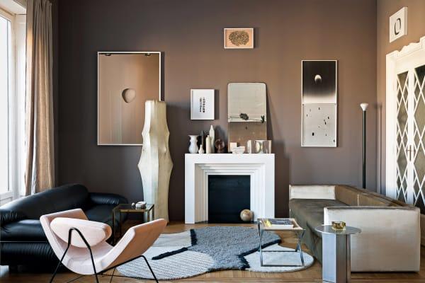 """Der Kaminsims im Wohnzimmer mit den Keramiken ist inspiriert von den Hausfluren der Nachbarschaft. Mit Sofa """"Sesann"""" und Leuchte """"Fantasma""""."""