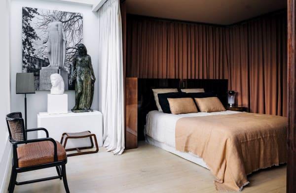 Tristan Auer gestaltet seinen Pariser Schlafbereich als Raum  im Raum. Rostbraune Vorhänge und ein Kopfteil aus Kupfer markieren die elegante Koje.