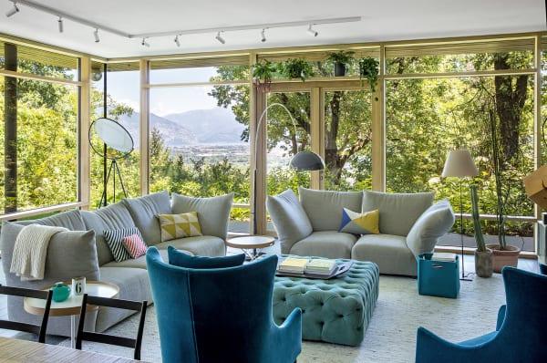 """Baumhaus: Die blauen Sessel von De Padova blicken im Wohnzimmerauf Wipfelgrün. Für den Rest der Familie stehen zwei Edra-Sofas bereit. Joe Colombos Leuchte """"Coupé"""" (Oluce) macht einen tiefen Bückling, Paolo Rizzattos """"Costanza"""" steht aufrecht."""