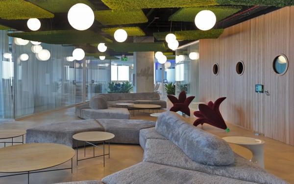"""Die Entscheidung des Designers, in den Meeting-Bereichen das vielseitige Mobiliar von Edra einzusetzen, passt zum hochflexiblen Bürokonzept: """"On the Rocks"""", die geschwungenen Sofaskulpturen in Kieselgrau mit beliebig versetzbaren Rückenlehnen und verschieden geformten Sitzflächen ermöglichen ihren Nutzern diverse Konfigurationen. Dank Rollen lassen sich die tiefroten Sessel-Lilien """"Getsuen"""" leicht bewegen."""